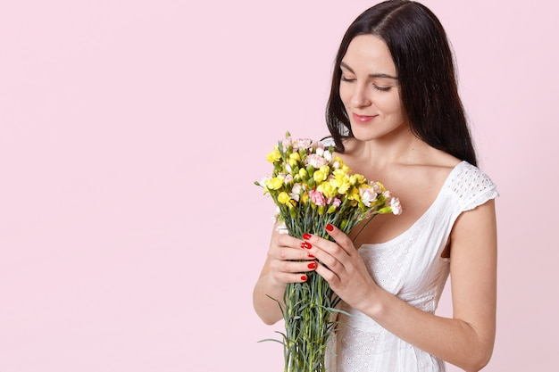 Portrait of tender attractive young woman with long black hair in summer white dress holding bouquet, smelling flowers