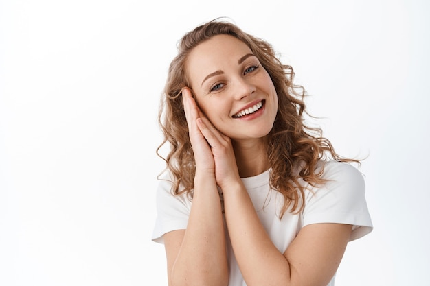 Portrait of tender blond girl, touching natural face with light make up, smiling happy and pleased, looking joyful at front, white wall