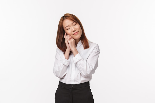 Portrait of tender and dreamy, romantic asian woman thinking about something silly, close eyes and touch cheek lean on hand dreaming about vacation with boyfriend,
