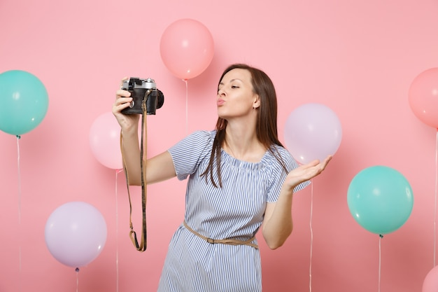 Portrait of tender happy woman in blue dress do selfie on retro vintage photo camera blowing lips kissing on pink background with colorful air balloons. birthday holiday party people sincere emotions.