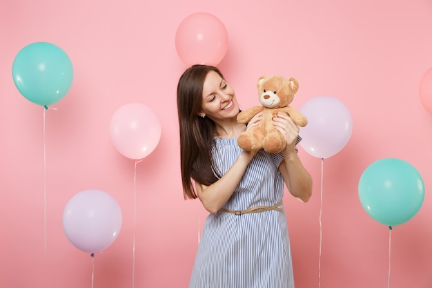 Portrait of tender joyful young woman in blue dress holding and looking at teddy bear plush toy on pink background with colorful air balloons. birthday holiday party, people sincere emotions concept.