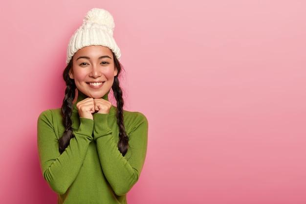 Ritratto di tenera e adorabile donna asiatica ha guance rosse, un sorriso piacevole, tiene le mani sotto il mento, guarda felicemente direttamente alla telecamera, indossa un cappello lavorato a maglia