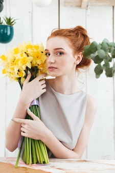 Portrait of tender redhead woman holding large bouquet