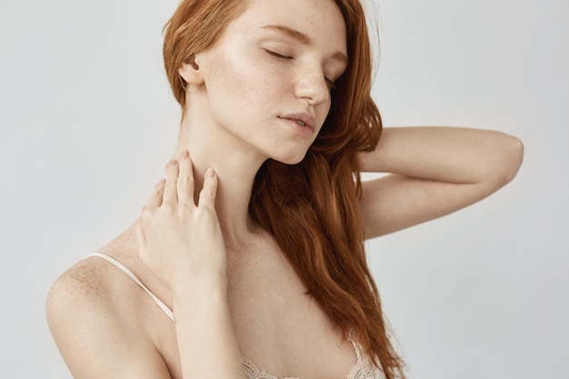 Portrait of tender redhead woman with freckles posing with closed eyes.