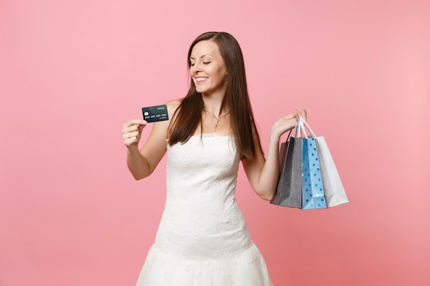 Portrait of tender woman in white dress holding credit card, multi colored packages bags with purchases after shopping