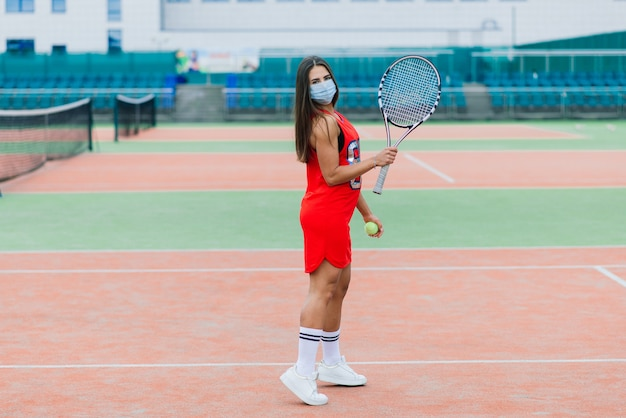 Portrait of tennis player girl holding racket outside with protective masks