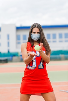 Portrait of tennis player woman holding a ball outside with protective masks