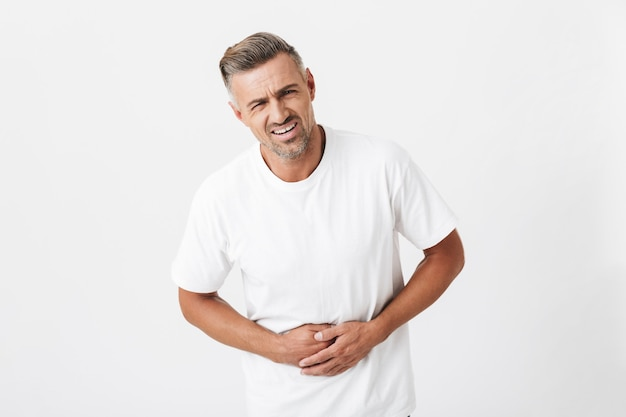 Portrait of tense man 30s with bristle wearing casual t-shirt touching his belly because of pain isolated on white