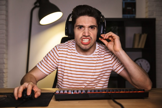 Portrait of tense young man 20s wearing headset screaming, while sitting at desk with computer in room and looking at monitor
