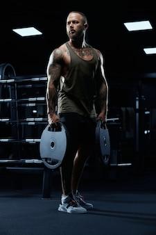 Portrait of tensed male bodybuilder in sportswear holding weights in arms.
