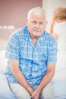 Portrait of tensed senior man sitting on bed