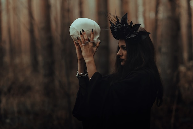 Portrait of a terrible witch with a skull in the hands of a dead man performs an occult mystical ritual in the forest