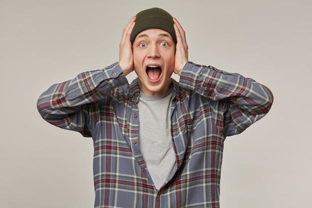 Ritratto di maschio adulto terrorizzato con capelli biondi. indossa una camicia a scacchi e un berretto, ha le bretelle. tenendogli la testa e urlando. concetto di emozione.