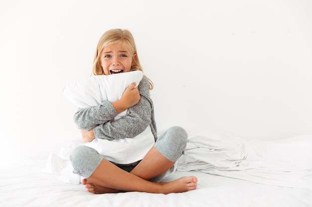Portrait of a terrified little girl hugging pillow