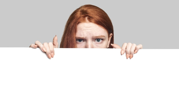 Portrait of terrified young redhead girl looking behind empty blank board and looking at camera