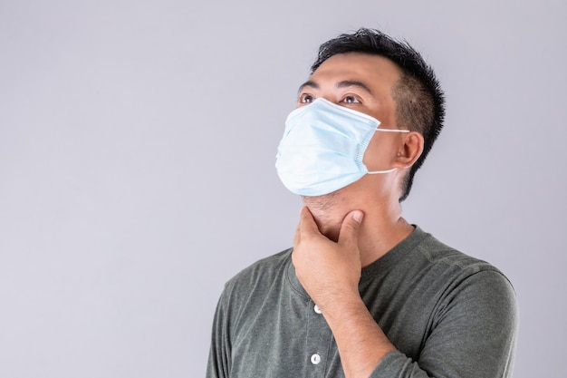 Portrait of thai patient wearing protective face mask and touching on his neck