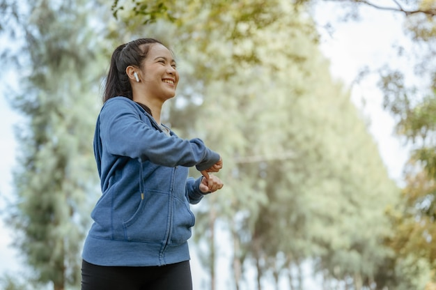 アジアの女の子が週末のエクササイズで運動し、自然の中で彼女の体を伸ばしている肖像画