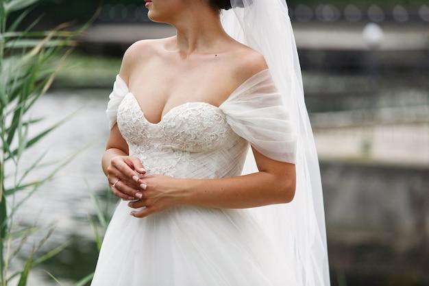 ネックラインと長いベールの屋外の結婚式の日の美しいウェディングドレスの花嫁の肖像画