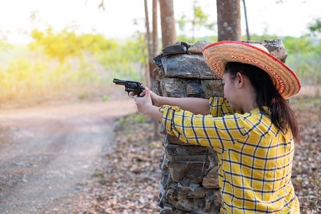 농장에서 오래 된 리볼버 총에서 총격 사건에 모자를 쓰고 농부 asea 여자 초상화