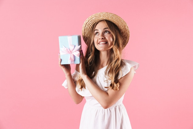 Portrait of thinking dreamy woman wearing straw hat looking upward and holding present box isolated over pink wall