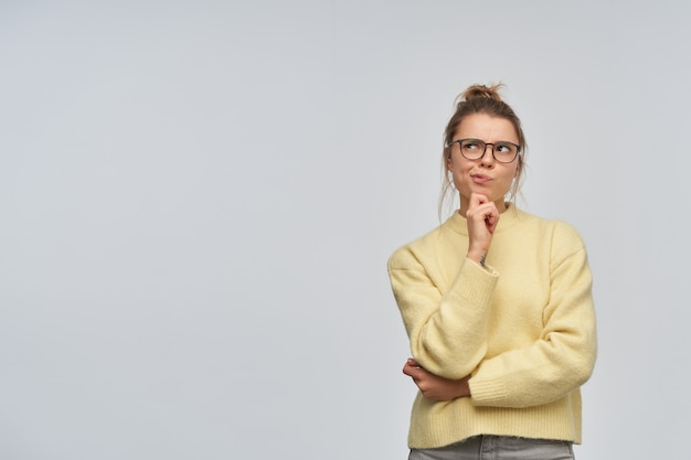 Portrait of thinking girl with blond hair gathered in bun. wearing yellow sweater and glasses. touching her chin and thoughtfully watching to the left at copy space, isolated over white wall