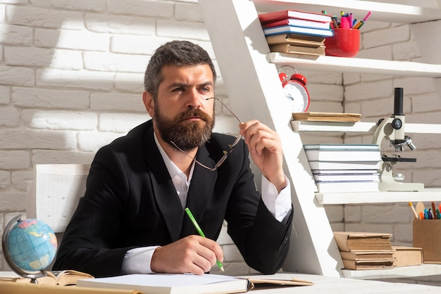 Portrait of thinking male teacher in school classroom. teacher sitting on desk writing text in book at school classroom.