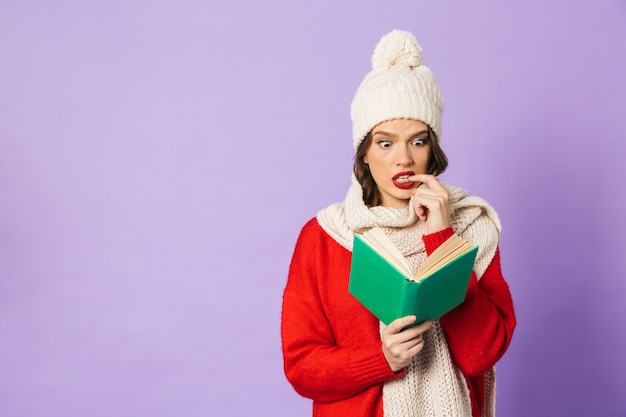 Portrait of thinking nervous young woman wearing winter hat isolated over purple wall reading book.