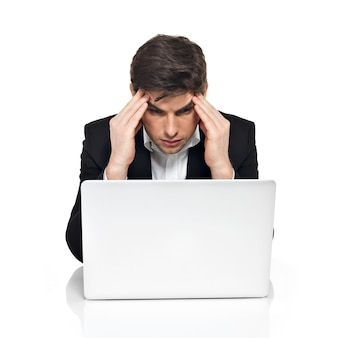 Portrait of thinking office worker with laptop having stress sitting on table, isolated on white.