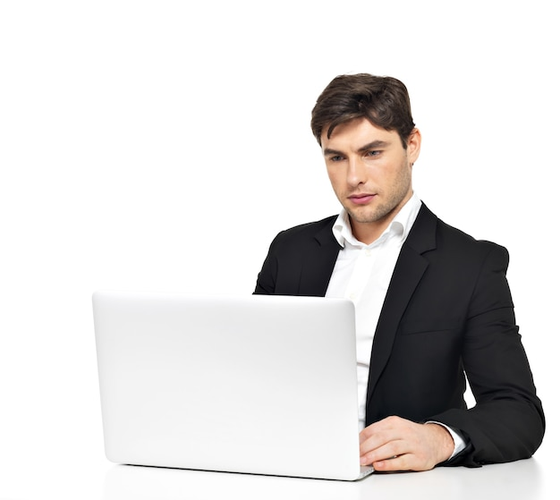 Portrait of thinking young office worker with laptop sitting on table isolated on white.