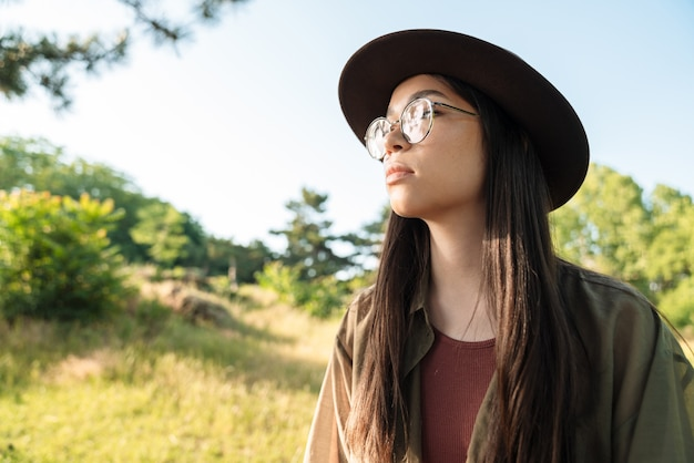 Portrait of thinking young woman with long dark hair wearing stylish hat and eyeglasses walking in green park on sunny day