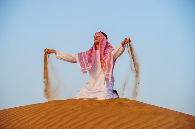 Portrait of thirsty arabic man on a middle of yellow desert.