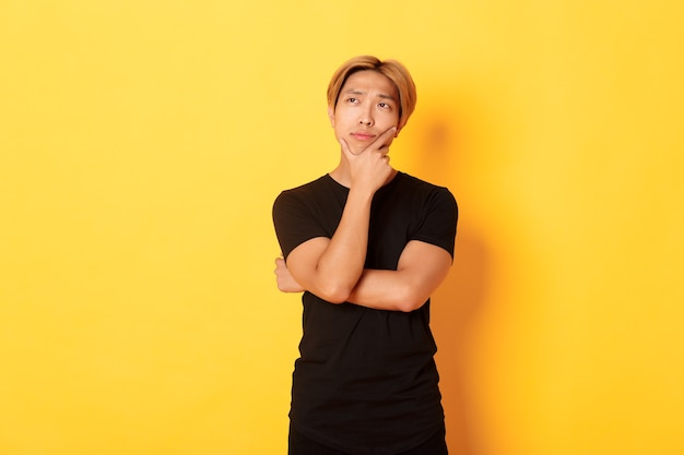 Portrait of thoughtful attractive guy in black t-shirt looking upper left corner. young man pondering idea, standing yellow wall