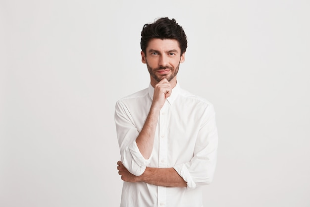 Portrait of thoughtful attractive young businessman with bristle wears shirt looks pensive and confident isolated on white keeps hands folded