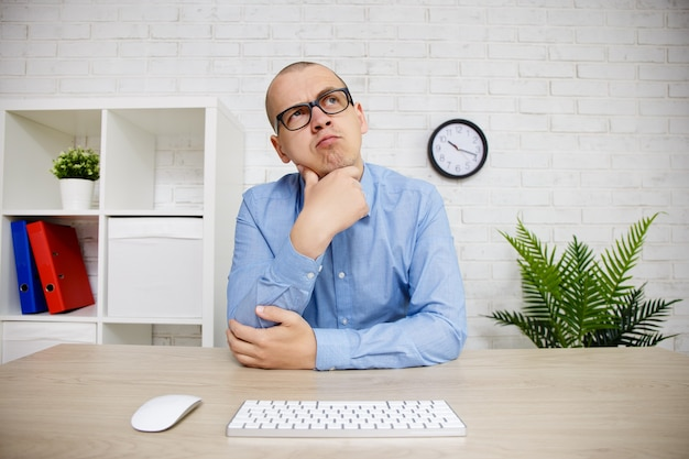 Portrait of thoughtful business man looking away while sitting at his working place in office