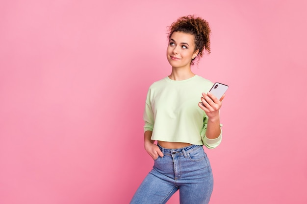 Portrait of thoughtful curious girl blogger use smartphone look copy space