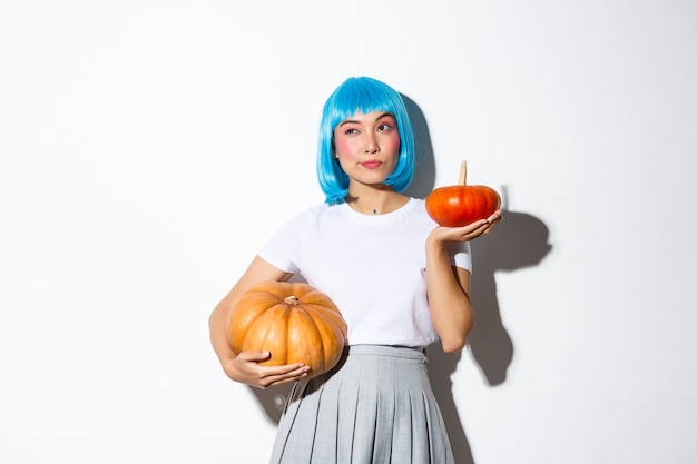 Portrait of thoughtful cute asian woman looking away while making choice, holding two different pumpkins, decorating halloween party, wearing blue wig.