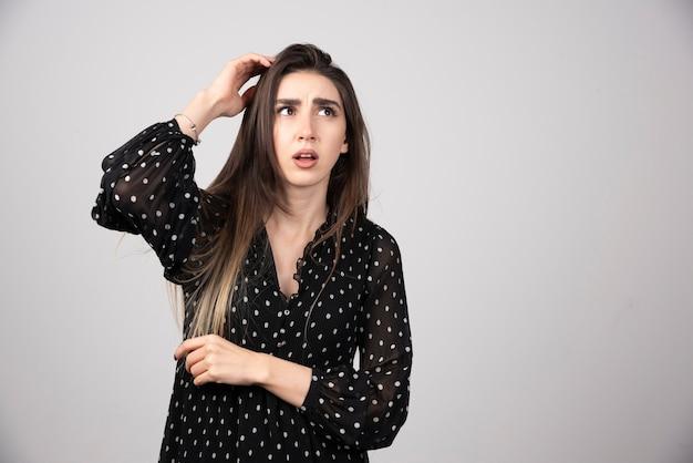Ritratto della ragazza premurosa che si tiene per mano sulla testa.