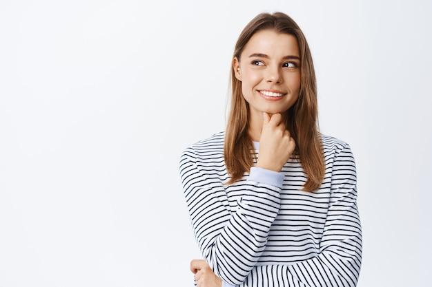 Ritratto di ragazza premurosa che fa ipotesi, ha idee interessanti, guarda a sinistra il logo dello spazio della copia e sorride, riflette, in piedi sul muro bianco