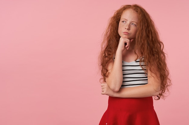 Portrait of thoughtful lovely girl with long curly foxy hair leaning her chin on raised hand and looking aside with folded lips, standing over pink background in red skirt and striped top