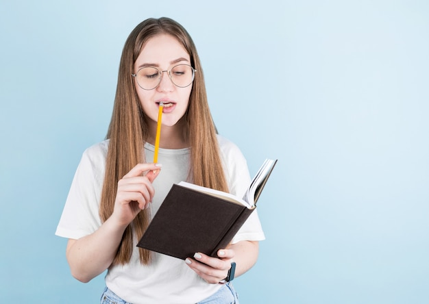 Portrait of thoughtful pensive girl having notebook and pencil in mouth. isolated on blue with copy space.