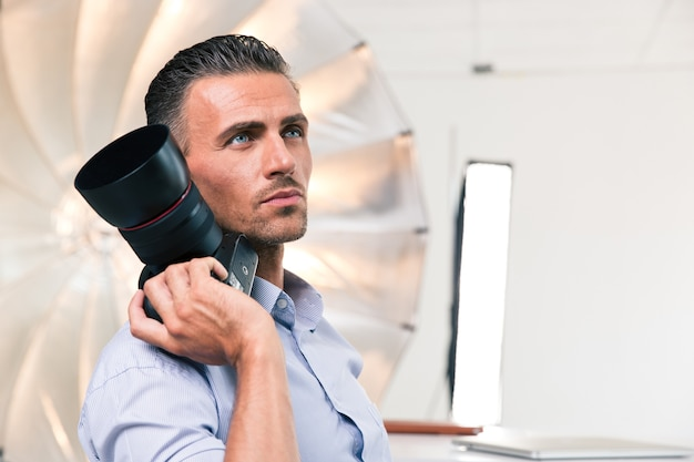 Portrait of a thoughtful photographer holding camera in studio