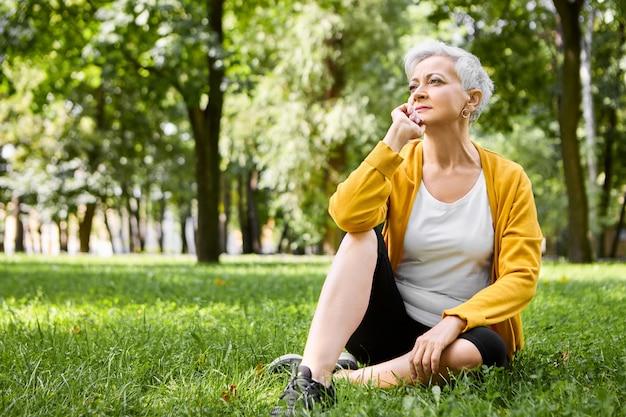 Ritratto di pensierosa donna in pensione in scarpe da corsa comodamente seduto sull'erba verde, tenendo la mano sotto il mento, guardando la gente camminare nel parco con espressione facciale pensierosa, sentendosi rilassato