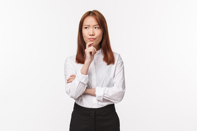 Portrait of thoughtful smart and creative businesswoman making plan, thinking how solve situation, touch chin and smirk while look away pondering,