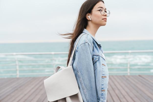 Portrait of thoughtful teenage girl wearing earpods and eyeglasses dreaming while walking along wooden pier by seaside