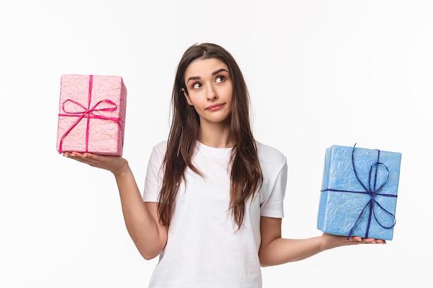 Ritratto di giovane ragazza premurosa che prende una decisione, cerca meravigliato, pesando scatole regalo nelle mani sparse lateralmente