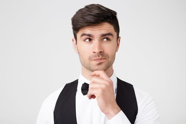 Ritratto di giovane premuroso che tiene la mano sul mento e distoglie lo sguardo in piedi isolato sopra il muro bianco