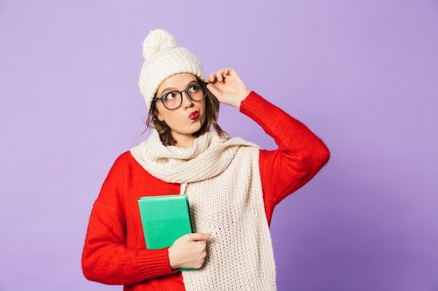 Portrait of a thoughtful young woman wearing winter hat isolated over purple wall reading book.