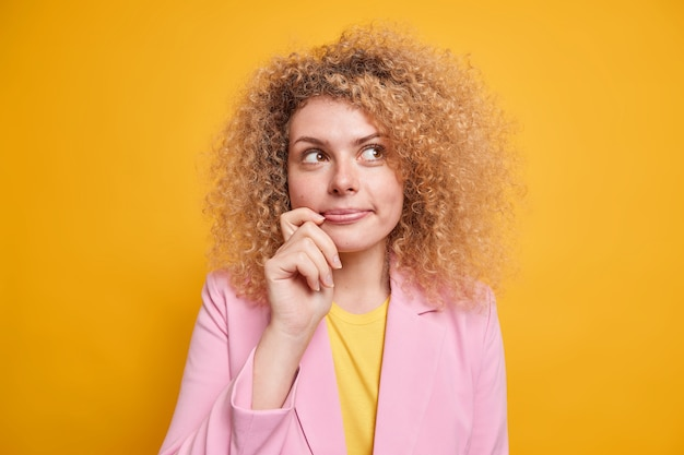 Portrait of thougthful young woman with curly hair looks aside with pleased pensive expression