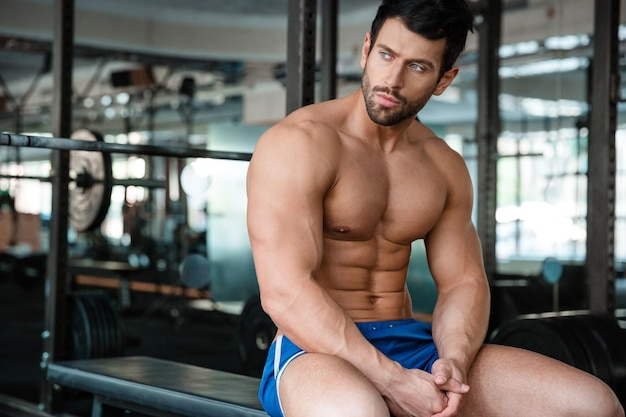 Portrait of a thouthful fitness man resting on the bench in gym