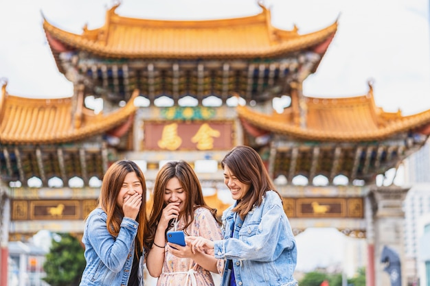 Portrait three asian happiness women laughing and using smart mobile phone